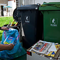 Man recycling paper, glass, plastic, cans and other rubbish in different containers, Belgium