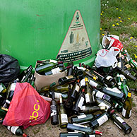 Glass collection point / Bottle bank with dumped wine bottles in front