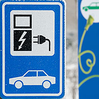 Electric car charging station sign at car park in the snow in winter, Belgium