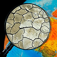 Cracked earth by drought seen through magnifying glass held against illuminated terrestrial globe