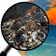 Nondegradable rubbish / refuse in water washed ashore seen through magnifying glass held against illuminated terrestrial globe