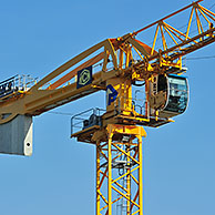 Yellow construction crane on building site showing cabin and counterweight, France