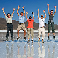 Tourists posing for camera while jumping in the air on the salt flat Salar de Uyuni, Altiplano, Bolivia