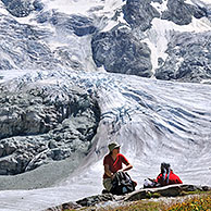 Walkers / Hikers resting with view over the Moiry Glacier in the Pennine Alps, Valais, Switzerland
