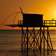 Traditional carrelet fishing hut with lift net on the beach at sunset, Loire-Atlantique, France
