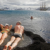 Tourists bathing in natural hot tub with volcanically heated water at Pendulum Cove, Deception Island, South Shetland Islands, Antarctica
