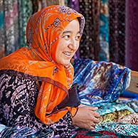 Kyrgyz woman with golden teeth selling colourful fabrics at market in Osh, Kyrgyzstan