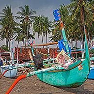 Colourful Indonesian jukungs, traditional wooden outrigger canoes on the Madewi beach along the Indian Ocean, Bali, Indonesia
