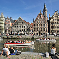 Tourists on quay along the river Lys with view over the Graslei / Grass Lane at Ghent, Belgium