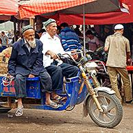 Uyghur farmers with motorized cart loaded with sheep at the cattle market in Kashgar / Kashi, Xinjiang, China
