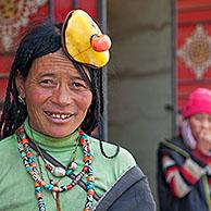 Portrait of Tibetan Khampa woman wearing traditional amber and red coral hair piece at Zhuqing, Sichuan Province, China
