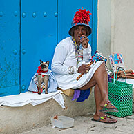 Licensed street model posing for tourists as colourful Cuban woman smoking huge Havana cigar with dressed cat in the streets of Old Havana / La Habana Vieja, Cuba