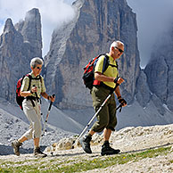 Couple of mountain walkers admiring the Tre Cime di Lavaredo / Drei Zinnen, Dolomites, Italy