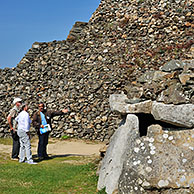 Tourists with guide visiting entrance to one of the chambers of the Cairn of Barnenez / Barnenez Tumulus / Mound, a Neolithic monument near Plouezoc'h, Finistère, Brittany, France