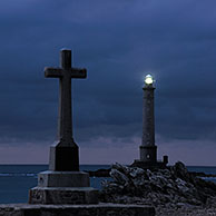 Cross and the lighthouse Phare de la Hague at night, Goury, Normandy, France