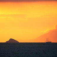 Sailing ship at sunset in front of the island Santiago, Galapagos