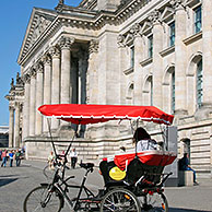 Taxi bike / rickshaw in front of the Reichstag building / Reichstag at Berlin, Germany