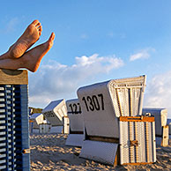Feet sticking out from roofed wicker beach chair at Sylt, North Frisian Island, Schleswig-Holstein, Germany