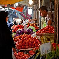 Iranian Muslim women wearing scarves buying vegetables and red tomatoes at food market booth in Gorgan / Gurgan, Golestan Province, Iran