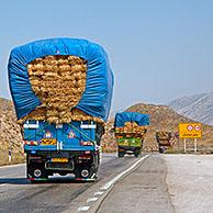 Convoy of heavily loaded trucks transporting bales of hay over highway in Iran