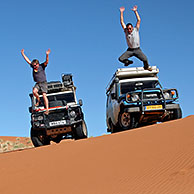 Four-wheel drive vehicles on sand dune in the Namib desert, Namibia, South Africa