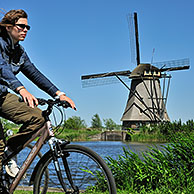 Cyclist and thatched windmill at Kinderdijk, a UNESCO World Heritage Site at South Holland, the Netherlands