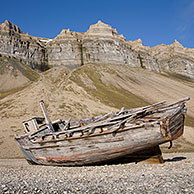 Wooden wrecked fishing boat stranded on shingle beach of Skansbukta, Svalbard, Spitsbergen