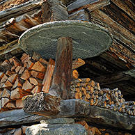 Detail of traditional wooden granary / raccard showing a circular stone slab to prevent rodents from gaining access to the grain or fodder reserves, Valais, Switzerland