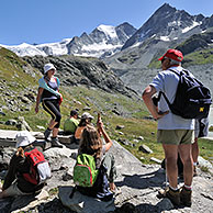 Tourists / Walkers walking along mountain path in the Pennine Alps, Valais, Switzerland
