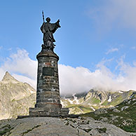 The statue of Saint Bernard in the mist at the Great Saint Bernard Pass in the Swiss Alps, Switzerland