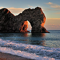 Durdle Door, a natural limestone arch at sunset along the Jurassic Coast near West Lulworth in Dorset, southern England, UK