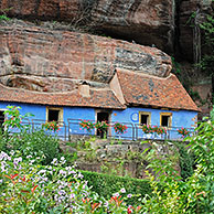 The blue troglodyte houses in rock face at Graufthal, Vosges, Alsace, France